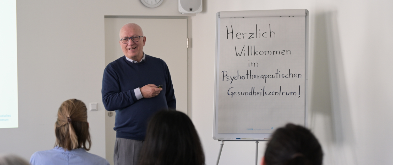 Prof. Dr. Zaudig heißt Teilnehmer einer Veranstaltung willkommen